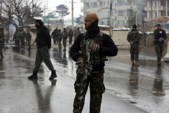 National army soldiers stand guard at the site of suicide attack near the military academy in Kabul, Afghanistan, Tuesday, Feb. 11, 2020.