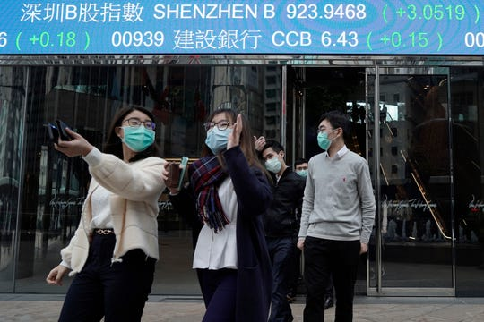 People wearing protective face masks, walk on a street in the Central, the business district of Hong Kong, Tuesday, Feb. 11, 2020.