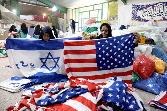 """Workers fold U.S. flags and Israeli flags with a slogan in Persian which reads, """"Death to Israel"""" Feb. 8 at the Diba Parcham Khomein factory in Heshmatieh village, a suburb of Khomein city, in central Iran."""