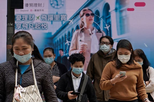 People wearing protective face masks walk on a street in the Central, the business district of Hong Kong, Tuesday, Feb. 11, 2020.