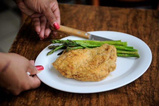 A fried pork chop with sauteed asparagus at Mele's Diner.