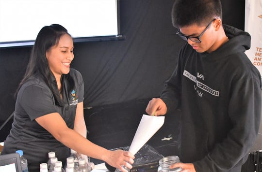 Lenora Makela, a registered dietitian nutritionist, works with student volunteer Gavin San Nicolas during the launch of the Athlete Awareness program Feb. 11 at Tiyan High School. The program is a partnership between the Guam Department of Education and the Guam National Olympic Committee.