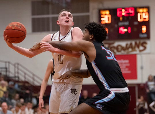 Webster County's Zaine Geary (11) is fouled by Union County's Clem Johnson (32) on a layup attempt at Webster County High School Monday night.