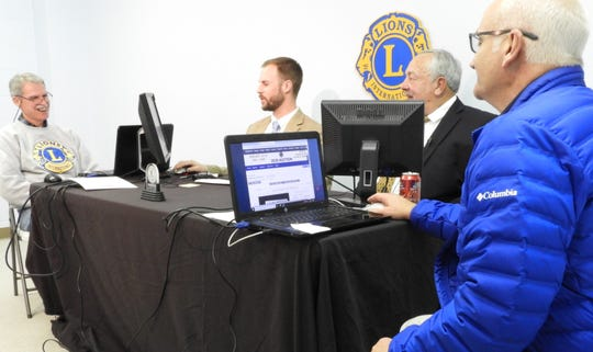 On-air Lions Club Auction hosts Evan Dixon and Mike Smith get some help from Don Wathen, far left, and Bill Oeth.