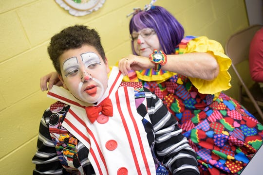 """Cayden Williams, who plays Superstar in the Sonshine Bunch clown ministry group, is helped by Susie Waddell while getting ready in the """"Clown Room"""" at Ridgeview Baptist Church in Knoxville, Tenn. on Sunday, Feb. 9, 2020."""