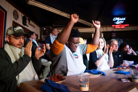 Tennessee offensive lineman Trey Smith celebrates his victory at winning the the hot wing eating competition at Wild Wing Cafe on Monday, February 10, 2020. At left is Adam Litton of NewsTalk 98.7. The competition was to celebrate the ongoing success of County Mayor Glenn Jacob's reading initiative, Read City USA.