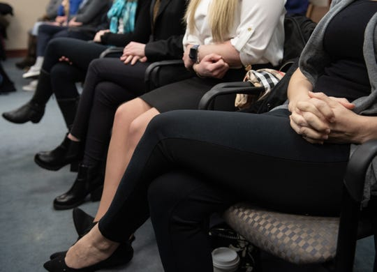 Nassar survivors clasp their hands while listening to a 2018 recording of an interview between investigators and former Michigan State University women's gymnastics coach Kathie Klages on Tuesday, Feb. 11, 2020, during the first day of testimony in Ingham County Circuit Court Judge Joyce Draganchuk's courtroom at Veterans Memorial Courthouse in Lansing, Mich.  Klages is on trial for two counts of lying to police during the 2018 interview.