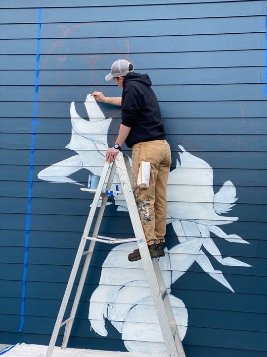 Emily LaForce paints primer on a mural she is creating at Saltwater Crab in Midtown Memphis.
