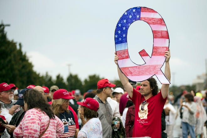 """David Reinert holds a Q sign while waiting in line to enter a campaign rally with President Donald Trump in Wilkes-Barre, Pa. on Aug. 2, 2018. QAnon is a conspiracy theory centered on the belief that Trump is waging a secret campaign against enemies of the """"deep state."""""""