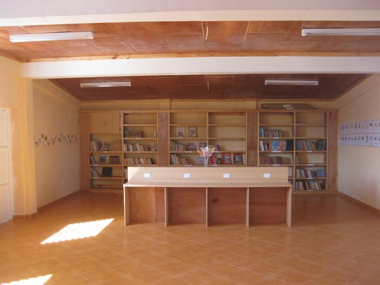 This photo from the Our Lady of Perpetual Help Orphanage Complex in Haiti shows one of two library alcoves with grad-appropriate books and computer carrels that separate it from study hall area. All shelving and built-ins built by local carpenters / cabinet makers.