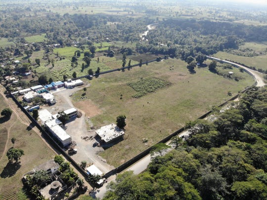 """An aerial view of  the Our Lady of Perpetual Help Orphanage Complex campus in Haiti shows (clockwise from upper left: children's residential complex; study hall / library [blue roof]; nun's residential quarters; clinic (at bottom - under construction), and K-6 school (""""L"""" shaped building designed around large mango tree)."""
