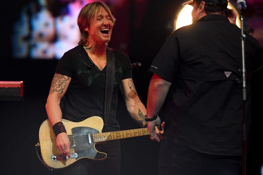 Keith Urban performs with Luke Combs during the All the Hall benefit concert at Bridgestone Arena in Nashville, Tenn., Monday, Feb. 10, 2020.