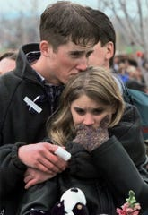 In this photo from April 25, 1999, Columbine High School shooting victim Austin Eubanks hugs his girlfriend during a community wide memorial service in Littleton, Colo., for the victims of the rampage the previous week. Eubanks was shot in his hand and knee and watched his best friend die.