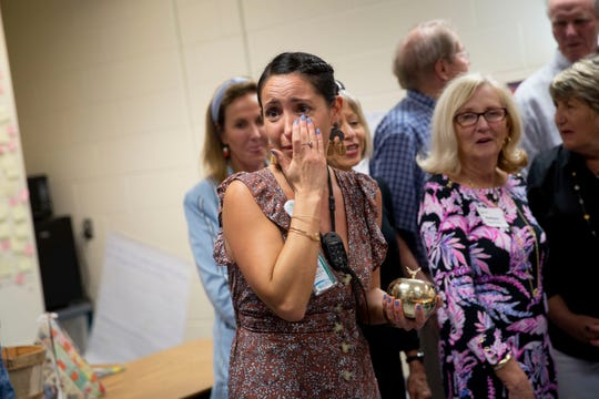 Eighth grade language arts and global perspectives teacher Elizabeth Garcia, center, wipes away tears between posing for photos during the surprise deliveries of Golden Apple awards at Manatee Middle School in East Naples on Tuesday, February 11, 2020.