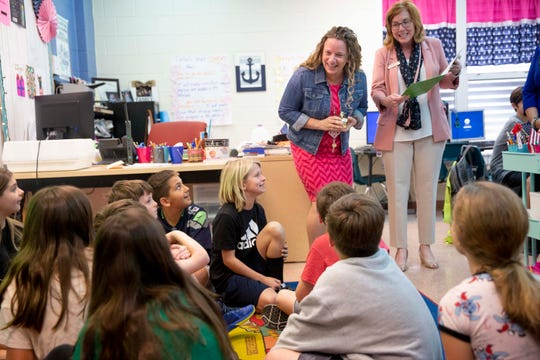 Fifth grade language arts and social studies teacher Theresa Golden, left, talks to her students after being presented with a Golden Apple during the surprise deliveries of Golden Apple awards at Veterans Memorial Elementary in Naples on Tuesday, February 11, 2020.