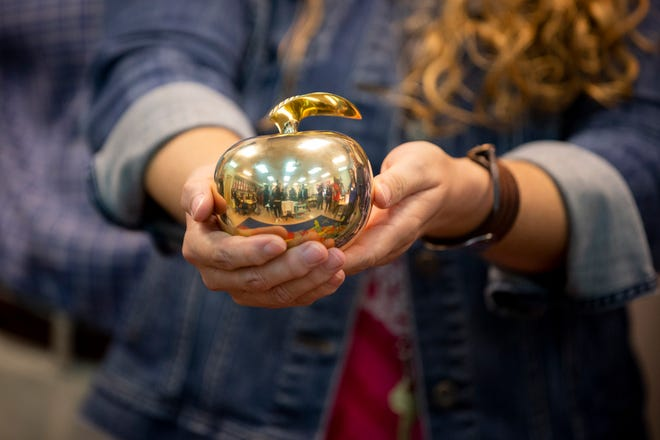 Fifth grade language arts and social studies teacher Theresa Golden holds out her Golden Apple during the surprise deliveries of Golden Apple awards at Veterans Memorial Elementary in Naples on Tuesday, February 11, 2020.