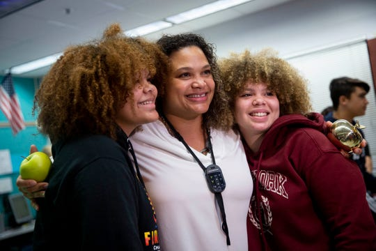 10th grade world history teacher Serena M. Hampton-Dunn, center, poses for a photo with her daughters, Zoë Terrero, left, and Samantha Terrero, right, after receiving a Golden Apple during the surprise deliveries of Golden Apple awards at Barron Collier High School in Naples on Tuesday, February 11, 2020.