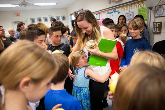Fifth grade language arts teacher Sarah Bratcher, center, hugs her daughter, Braelynn Bratcher, 5, after being presented with a Golden Apple during the surprise deliveries of Golden Apple awards at Lake Park Elementary in Naples on Tuesday, February 11, 2020.