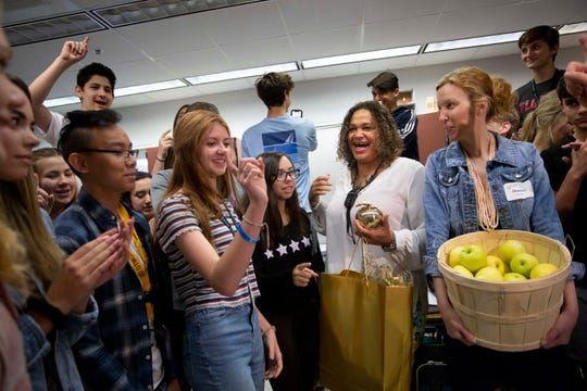 10th grade world history teacher Serena M. Hampton-Dunn, center, laughs with her students after receiving a Golden Apple during the surprise deliveries of Golden Apple awards at Barron Collier High School in Naples on Tuesday, February 11, 2020.