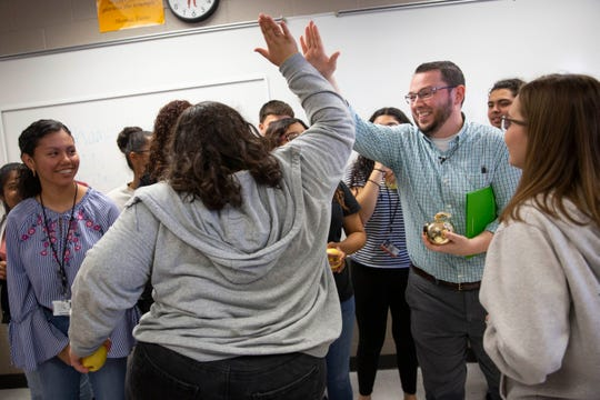 "Eleventh grade U.S. history teacher David Stehlin, right, high fives Ariana Gallegos, center, after being presented with a Golden Apple during the surprise deliveries of Golden Apple awards at Immokalee High School in Immokalee on Tuesday, February 11, 2020. Gallegos says she asks Stehlin for a high five every time she comes to his class, but this is the first time he's given in. ""I finally get a high five!"" she said."
