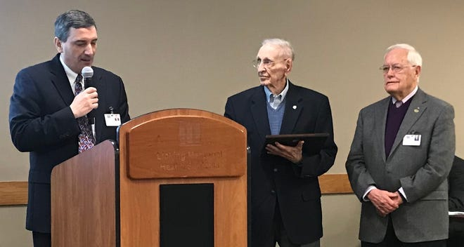Licking Memorial Health Systems President and CEO Rob Montagnese (left) presents former LMH board member Jack Crockford  (middle) with the Robert McGaughy Honorary Ambassador Award for service to LMHS at Tuesday's LMH breakfast. McGaughy is on the right.
