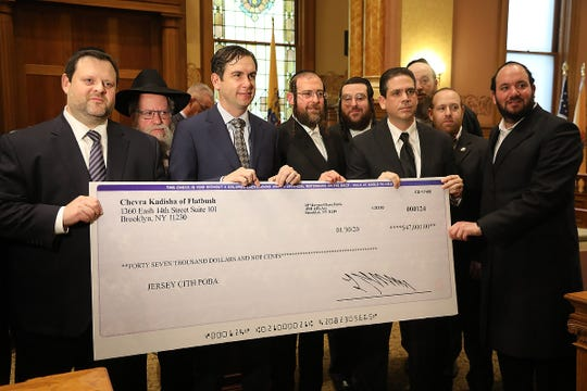 Chaskel Bennett co founder of the Flatbush Jewish Community Coalition presents a check to Jersey City Mayor Steven Fulop and POBA President Carmine Disbrow. The $47,000 check is for the family of the family of slain Jersey City police officer Joseph Seals who was killed in December.