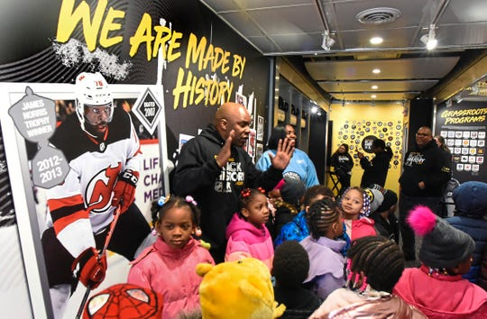 "Students from the Pittsburgh Miller Pre-K African-Centered Academy listen to Kwame Mason talk about ""Herb Carnegie"" in the NHL's Black Hockey History mobile museum, along Bedford Avenue, Friday, Jan. 31, 2020, in the Hill District of Pittsburgh. Carnegie was a Canadian ice hockey player and started one of Canada's first hockey schools."