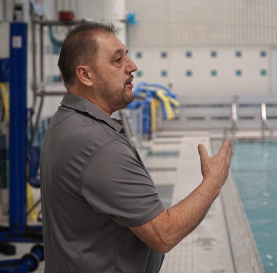 Novi High School diving coach Don Mason talks to a student about their form during a Feb. 11, 2020 practice at the school.
