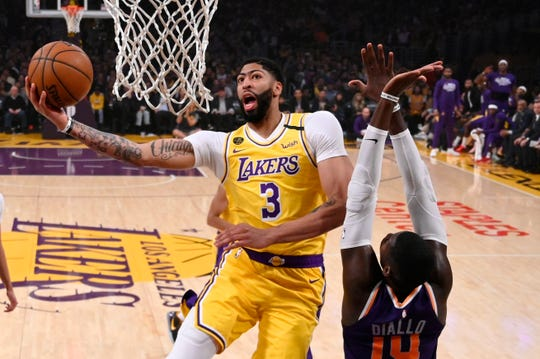 Los Angeles Lakers forward Anthony Davis, left, shoots as Phoenix Suns forward Cheick Diallo defends during the first half of an NBA basketball game Monday, Feb. 10, 2020, in Los Angeles. (AP Photo/Mark J. Terrill)