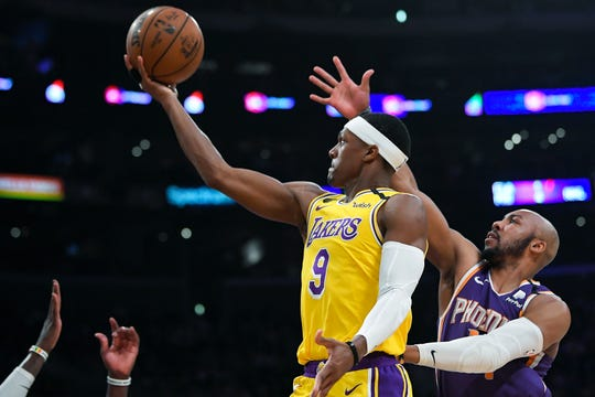 Los Angeles Lakers guard Rajon Rondo, left, shoots as Phoenix Suns guard Jevon Carter defends during the second half of an NBA basketball game, Monday, Feb. 10, 2020, in Los Angeles. The Lakers won 125-100. (AP Photo/Mark J. Terrill)