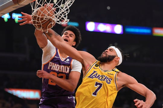 Phoenix Suns forward Cameron Johnson, left, dunks as Los Angeles Lakers center JaVale McGee defends during the first half of an NBA basketball game Monday, Feb. 10, 2020, in Los Angeles. (AP Photo/Mark J. Terrill)