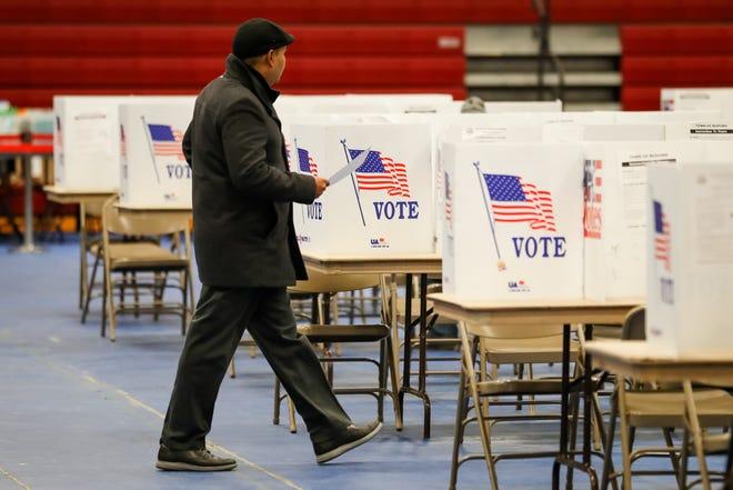Un hombre de aproxima a las urnas a depositar su voto.