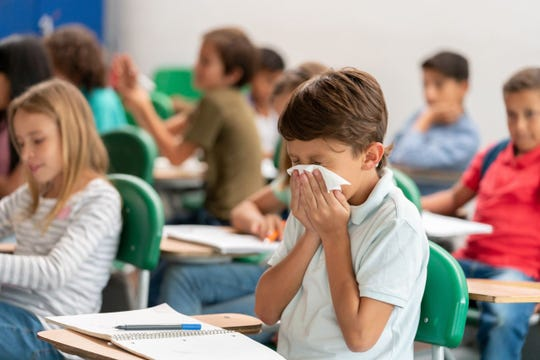 A child sneezes into a tissue in a classroom.