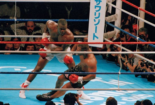 FILE - In this Feb. 11, 1990, file photo, James Douglas, left, follows with a left, dropping Mike Tyson to the canvas in the 10th round of scheduled 12-round heavyweight champion bout at the Tokyo Dome in Tokyo. In one of the more spectacular upsets in sports history, Douglas defeated Tyson, the reigning world heavyweight champion. (AP Photo/Tsugufumi Matsumoto, File)