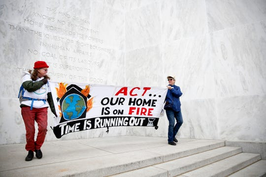 Debby McGee, left, and Patty Hine, both of Eugene, dance with a banner as about 1,000 carbon cap-and-trade bill supporters rally at the Oregon State Capitol in Salem on Feb. 11, 2020. Senate Bill 1530 would impose an economy-wide cap on carbon emissions and charge the stateÕs largest polluters for emissions over the limit.