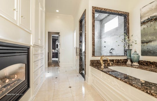 A serene master bath features a fireplace and luxurious style.