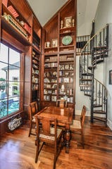 A discreet spiral staircase is tucked beside the walls of books in the library.