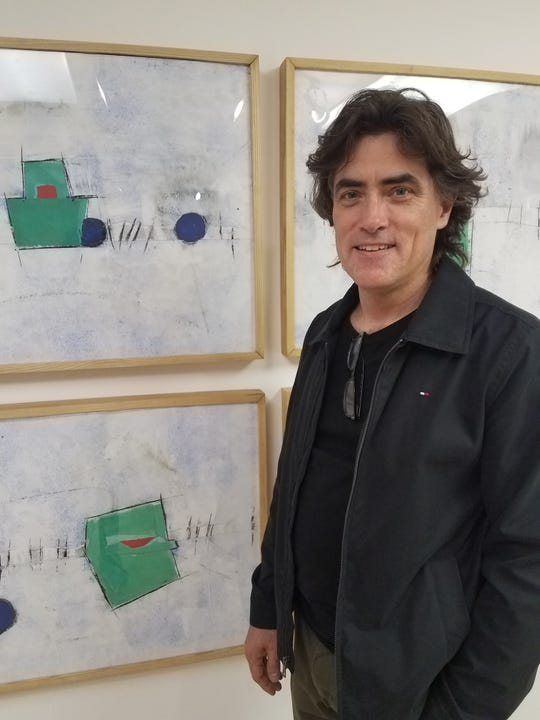 Artist Michael Hunnewell with one of his paintings inspired by musical notation at the Anders-Brickler Gallery.