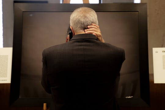 """Gary Vien clenches the back of his neck with his right hand, with a listening device to his ear with his left, holding back tears as he hears the voice of Ronit Reoven, a Marjory Stoneman Douglas High School teacher, who recalls how she tried her best to hide in 31 students in her classroom the day a gunman opened fire in the school, killing 17, including one that died instantly after being shot in her classroom.   Vien was speechless after looking through the collection of six of the 52 stories of the shooting victims that make up """"Anguish in the Aftermath"""" on display at the Capitol in recognition of the two year anniversary until Friday, Feb. 14, 2020."""