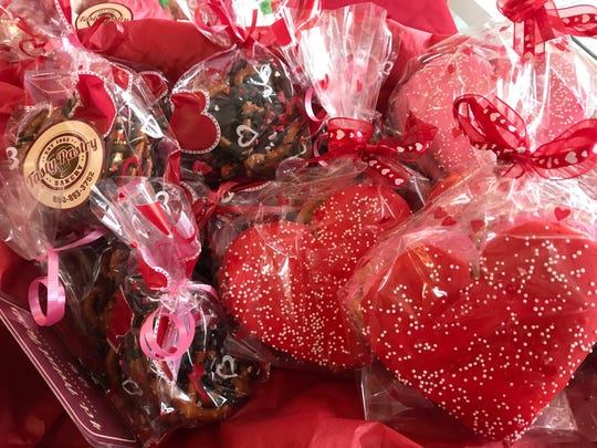 Valentine's Day specialties including cakes, sugar cookies and cupcakes, many sporting red sprinkles and tiny hearts at Tasty Pastry.