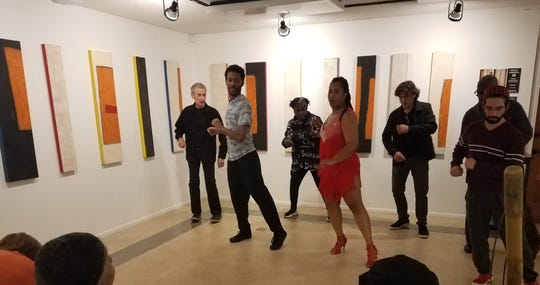 Miriam Watkins of Studio D leads a group of museum-goers in salsa moves set to the rhythmic notations portrayed in Michael Hunnewell's abstract art on exhibit at the Anderson Brickler Gallery on Feb. 7, 2020.