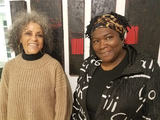 Dr. Celeste B. Hart, founder of the Anderson-Brickler Gallery and Kabuya Bowens-Saffo, senior administrative curator before a painting by Michael Hunnewell where his exhibition is paired with music and dance.