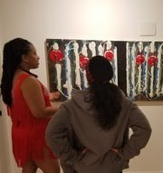 Before beginning a lesson in salsa rhythms and technique, Miriam Watkins from Studio D explains the rhythmical meaning of Michael Hunnewell's painting to a viewer at the Anderson Brickler Gallery. The museum is expanding its vision to include not only art, but music, dance, and the written word.