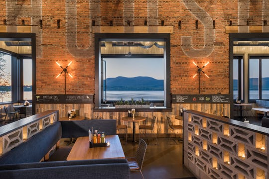 The semi-industrial space offers soaring ceilings, historic herringbone and soldier brick patterns, exposed ducts, reclaimed wood, colorful tiles and basket-like pendants.