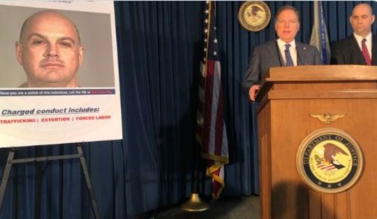 Geoffrey Berman, U.S. Attorney for the Southern District of New York, describes the allegations against Lawrence Ray, seen in poster at left, Feb. 11, 2020.