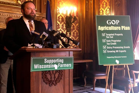 Wisconsin Assembly Rep. Tyler August speaks at a news conference attended by other GOP lawmakers to unveil a pair of tax cuts and other plans designed to help the state's struggling agriculture industry on Monday, Feb. 10, 2020, in Madison, Wis. The Capitol news conference to unveil the bills came a day before a public hearing was scheduled on the measures. (AP Photo by Scott Bauer)