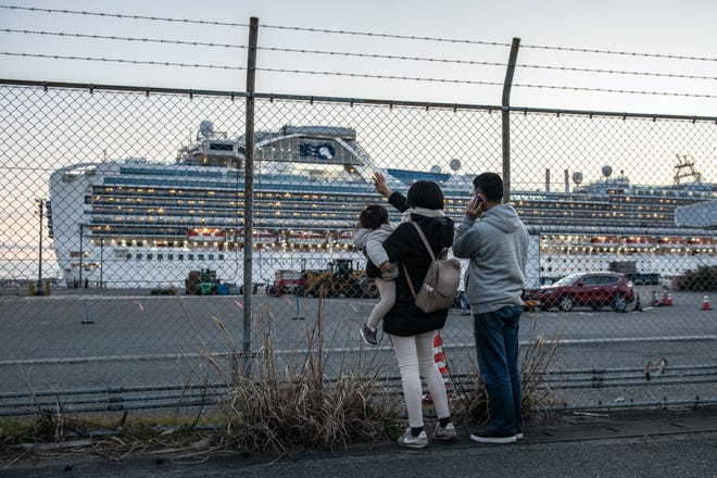 Relatives of Diamond Princess passengers wave towards the quarantined cruise ship at Daikoku Pier Cruise Terminal in Yokohama, Japan. The ship went out to sea Tuesday to dump wastewater and generate potable water.