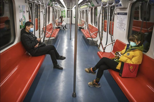 People wear protective masks as they ride on a nearly empty subway car during the evening rush period on Feb. 10, 2020 in Beijing, China.