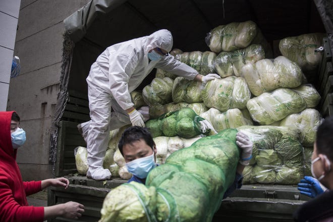 Employees wear a protective masks whilst carrying vegetables from trucks at a hospital on Feb. 10, 2020 in Wuhan, China.