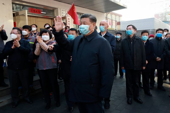 In this photo released by Xinhua News Agency, Chinese President Xi Jinping, centre, wearing a protective face mask, waves as he inspects the novel coronavirus pneumonia prevention and control work at a neighborhoods in Beijing, China, on Feb. 10, 2020.